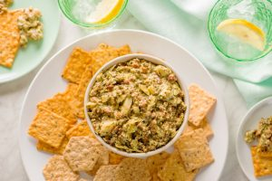 Crunchmaster Multi-Grain crackers with creamy artichoke and bacon pesto.