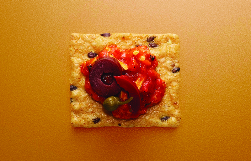 Crunchmaster cracker with red salsa and olives on top.