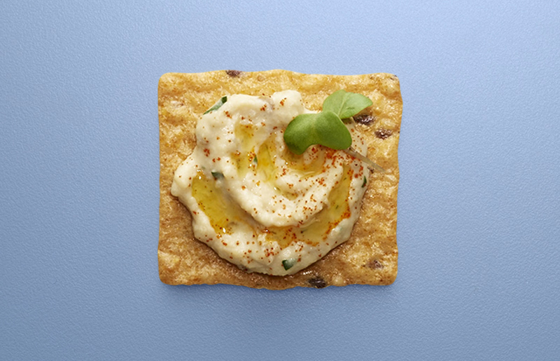 Crunchmaster cracker with hummus on top.