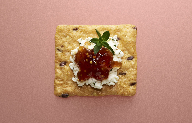 Crunchmaster cracker with cheese and jam on top.