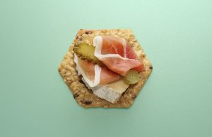 Crunchmaster cracker with prosciutto and brie on top.
