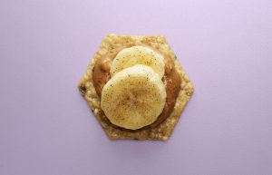 Crunchmaster cracker with peanut butter and bananas on top.
