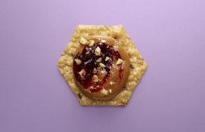 Crunchmaster cracker with peanut butter and jelly on top.