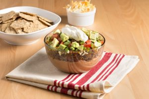 Layered taco dip with Crunchmaster crackers for dipping.